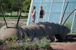 "Grandkids play on the 30 foot long ""Lopatapillar"", a creation by artist Bob Cassilly"