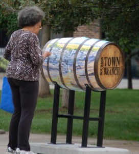 A person looks at the artwork on a barrel in downtown Lexington